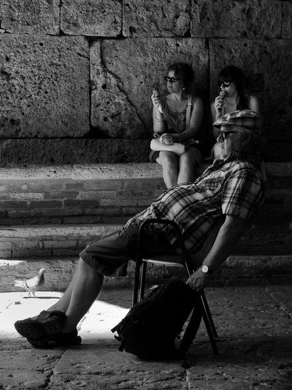 FujifilmX20 -f/5,6 -1/30 -ISO100  En la pequeña localidad de Sangimignano en italia, es una tarde de verano y hace un calor asfixiante. Un hombre mayor aprovecha para resguardarse a la sombra en una galería en frente de la antigua catedral.
