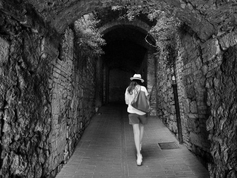 Fujifilm X20 -f/3,2 -1/13 -ISO200 En Sangimignano, pintoresco pueblo de la Toscana italiana, una turista pasea en medio de las callejuelas que conforman el casco antiguo de este pequeño enclave.