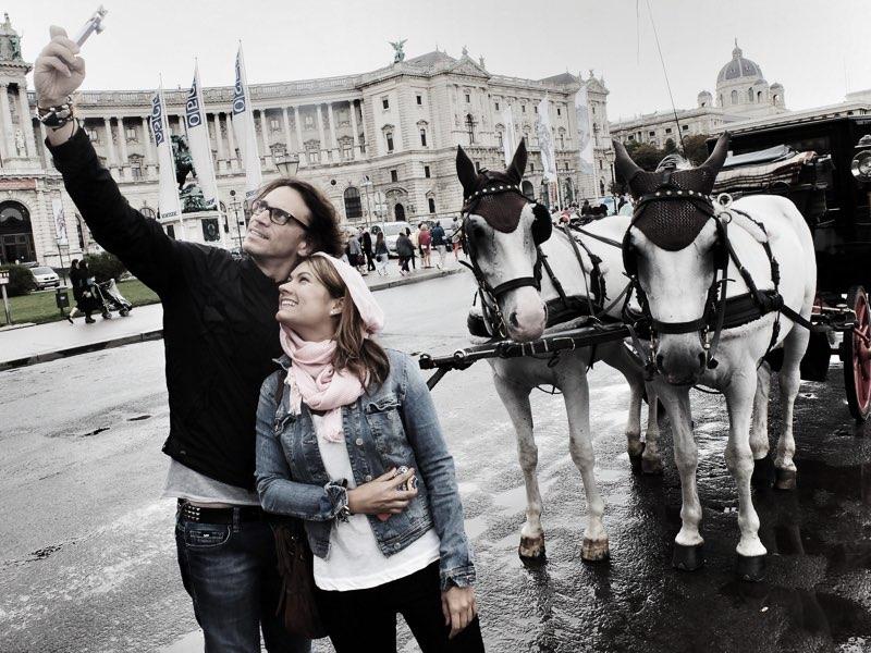 Fujifilm X20 – f/7,1 – 1/50 – ISO200 Una pareja de turistas hace un selfie con los caballos y sus carruajes, en la plaza de Heldenplatz.